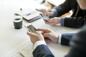 スマートフォンを操作するビジネスマンたち