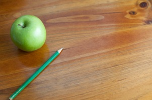 School desk with pencil and apple