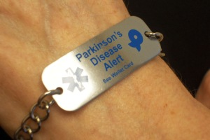 Beth Lee, 62, shows a bracelet identifying her as a Parkinson's patient.