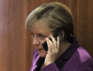 File photo of Germany's Chancellor Merkel using her mobile phone before a meeting at a European Union summit in Brussels